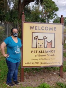 """A woman in a blue T-Shirt is standing in front of a sign saying """"Welcome Pet Alliance"""". The sign depicts a dog and a cat."""