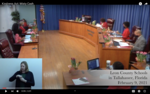 A screenshot of the beginning of a YouTube video-- the one linked in the article. The screenshot shows the school board meeting beginning, with the date and location visible in the bottom right corner. An ASL interpreter is present in the bottom left corner.