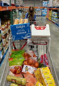 A shopping cart filled with food, pushed by a girl with long hair wearing a black face mask.