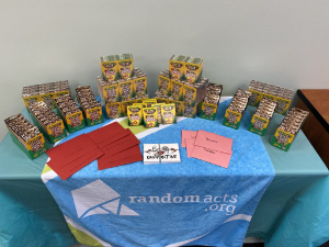Boxes of Colors of the World crayons displayed on a table. A banner spread over the table cloth shows the Random Acts logo and website. Valentine cards are also present on the table
