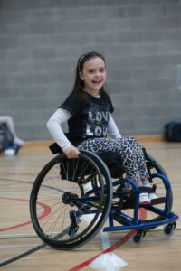 A young girl uses a wheelchair to participate in basketball practice. She smiles at the camera.