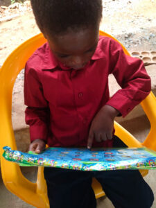 A small Ghanaian boy admires his new writing board