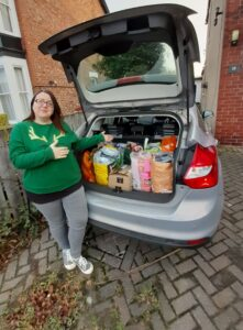 a woman in a green sweatshirt standing next to a gray vehicle with an open trunk filled with bags and boxes of donations
