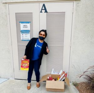 a person wearing a blue shirt, black pants, and a black mask next to a box filled with food donations