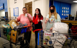 Three women standing behind two shopping carts full of kitchen supplies with their thumbs up