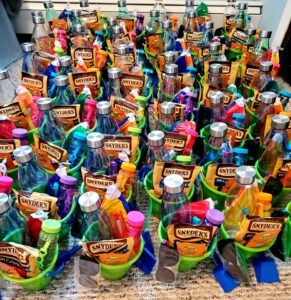 a bunch of green and yellow buckets filled with pretzels and sun toys