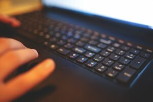 A blurry image of two hands tapping away on the keyboard of a computer