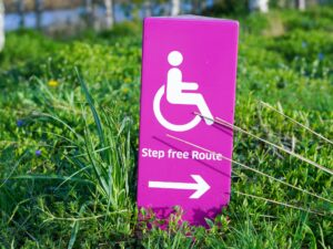 """A pink sign sits in the grass. On the sign is a wheelchair symbol, with the words """"step free route"""" written under it. Below the words is an arrow pointing to the right."""